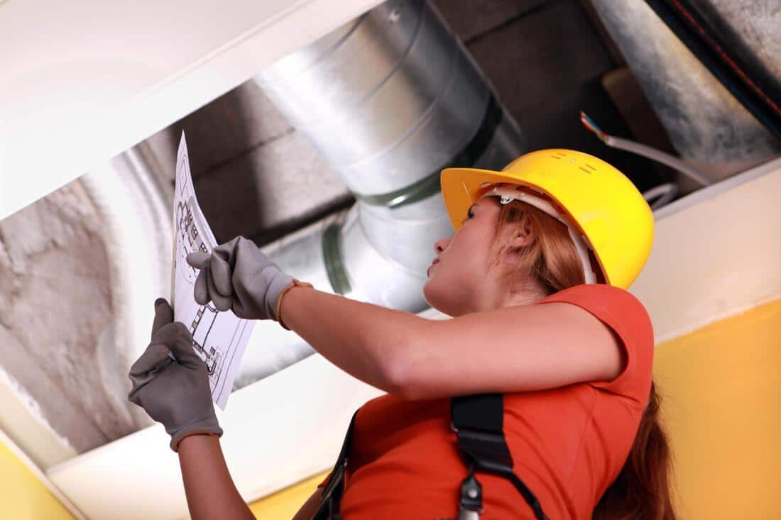 A woman inspecting a commercial air duct system