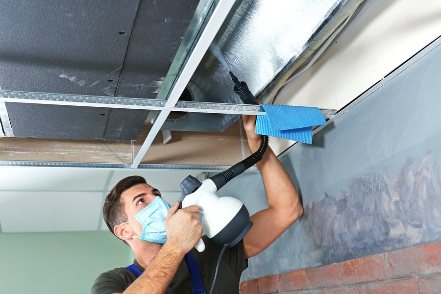 A Man with Mask Spraying Air Duct Pipe
